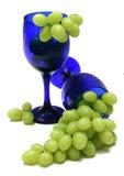 Uvas y vidrios azules Imágenes de archivo libres de regalías