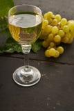 uvas y vino amarillos en el vidrio Imágenes de archivo libres de regalías