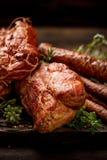 Uwędzeni mięsa i kiełbasy z dodatków świeżymi aromatycznymi ziele, zakończenie w górę zdjęcia stock