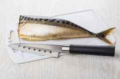 Uwędzona makrela na tnącej desce i kuchenny nóż na stole Fotografia Stock