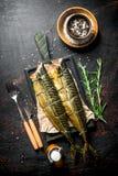 Uwędzona makrela na tnącej desce z rozmarynami i pikantność w pucharze zdjęcie stock