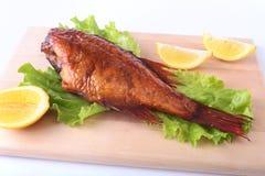 Uwędzona ryba i cytryna na zielonych sałata liściach na Drewnianej tnącej desce na białym tle Zdjęcie Stock