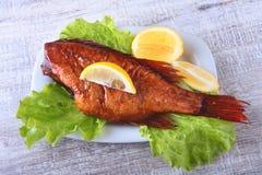 Uwędzona ryba i cytryna na zielonych sałata liściach na Drewnianej tnącej desce na białym tle Zdjęcie Royalty Free