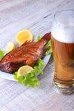 Uwędzona ryba i cytryna na zielonych sałata liściach na Drewnianej tnącej desce i szkle z piwem na białym tle Zdjęcie Royalty Free