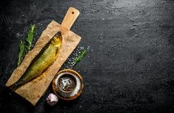 Uwędzona ryba na papierze z pikantność, rozmarynami i czosnkiem, zdjęcie royalty free