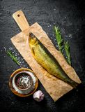 Uwędzona ryba na papierze z pikantność, rozmarynami i czosnkiem, fotografia stock
