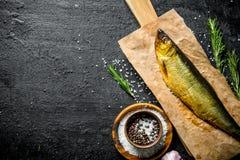 Uwędzona ryba na papierze z pikantność, rozmarynami i czosnkiem, obraz royalty free