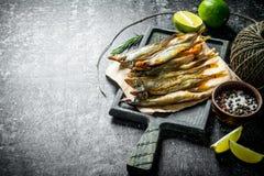 Uwędzona ryba na papierze z wapno plasterkami, pikantność i starą dratwą, fotografia stock