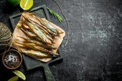 Uwędzona ryba na papierze z wapno plasterkami, pikantność i starą dratwą, fotografia royalty free