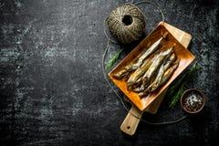 Uwędzona ryba na tnącej desce z pikantność i dratwą fotografia stock
