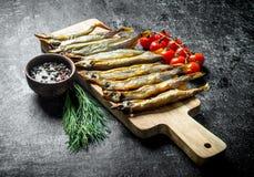 Uwędzona ryba na tnącej desce z pomidorami, koperem i pikantność, zdjęcia stock