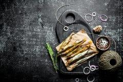 Uwędzona ryba na tnącej desce z rozmarynami, dratwą, pikantność i czosnków cloves, obraz royalty free
