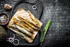 Uwędzona ryba na tnącej desce z rozmarynami, dratwą, pikantność i czosnków cloves, zdjęcia royalty free