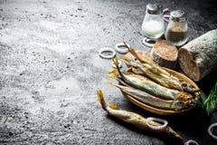 Uwędzona ryba z pokrojonym chlebem, pikantność i cebulkowymi pierścionkami, zdjęcia royalty free