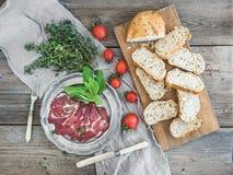 Uwędzony mięso w rocznika srebnym talerzu z świeżym basilem, pomidorami i chlebów plasterkami nad nieociosanym drewnem, Zdjęcia Royalty Free