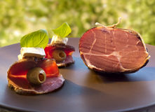 Uwędzony wysuszony gammon baleron i startery z oliwkami, serem i basilem na brown plater agaist, zieleniejemy tło (kanapka) Obraz Royalty Free