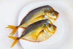 Uwędzona ryba na bielu talerzu na tle Obrazy Royalty Free