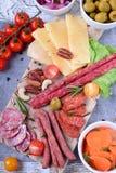Uw?dzony kie?basa asortyment, ser, dokr?tki, czere?niowi pomidory, kiszeni warzywa i oliwki na bia?ym drewnianym stole, fotografia royalty free