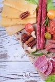 Uw?dzony kie?basa asortyment, ser, dokr?tki, czere?niowi pomidory, kiszeni warzywa i oliwki na bia?ym drewnianym stole, obraz stock