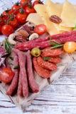 Uw?dzony kie?basa asortyment, ser, dokr?tki, czere?niowi pomidory, kiszeni warzywa i oliwki na bia?ym drewnianym stole, zdjęcie royalty free