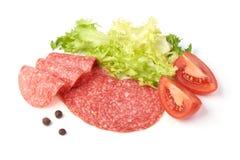 Uw?dzony salami z zielon? sa?at?, pomidorami i pikantno?? odizolowywaj?cymi na bia?ym tle, fotografia royalty free