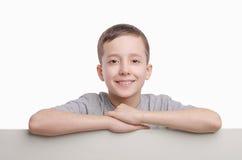 Uw Tekst hier Glimlachende jongen die zich dichtbij lege lege raad bevinden Emo royalty-vrije stock foto's