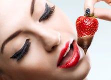 Uwiedzenie - czerwone żeńskie wargi je czekoladowe truskawki obrazy stock