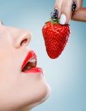 Uwiedzenie - kobiety usta je truskawki Fotografia Royalty Free
