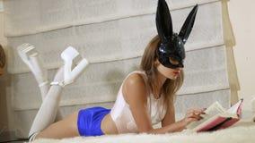 Uwodzicielska królik dziewczyna czyta książkowy kłaść na podłoga zbiory wideo