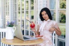 Uwodzicielska młoda brunetka Europejskiego pojawienie, pracuje na laptopie, pije jej wyśmienicie jagodowego koktajl, deser zdjęcia royalty free