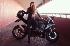Uwodzicielska rowerzysta dziewczyna opiera na jej superbike na chodniczku wśrodku mostu na słonecznym dniu obraz stock