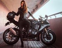 Uwodzicielska rowerzysta dziewczyna opiera na jej superbike na chodniczku wśrodku mostu na słonecznym dniu fotografia royalty free