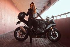 Uwodzicielska rowerzysta dziewczyna opiera na jej superbike na chodniczku wśrodku mostu na słonecznym dniu zdjęcie royalty free