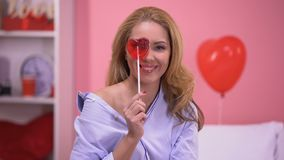Uwodzicielski blond damy przymknięcia oko z sercowatym lizakiem, ono uśmiecha się kamera zdjęcie wideo