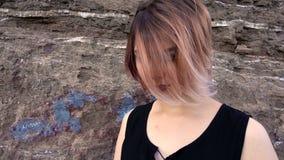Uwodzicielski dziewczyny blisko skały krajobraz dokąd jej włosiany dmuchanie w wiatrze zbiory wideo