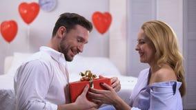 Uwodzicielski młody żeński daje czerwony prezenta pudełko zdziwiony chłopak, rocznica zbiory