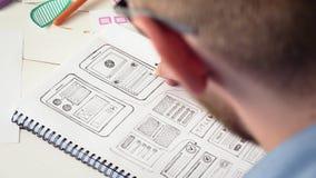 UX σχεδιαστής που σκιαγραφεί το πρωτότυπο νέο app στο σημειωματάριό του απόθεμα βίντεο
