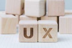 UX-de ontwikkeling, het ontwerpconcept van de Gebruikerservaring, kubeert houten blok die acroniem UX op gridlinenotitieboekje co stock foto