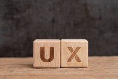 UX-het ontwerp van de Gebruikerservaring in product en de dienstconcept, kubeert houten blok de bouwacroniem UX op lijst met bord royalty-vrije stock afbeeldingen