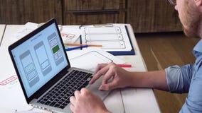 UX märkes- skapande mobil app prototyp på hans bärbar datordator arkivfilmer