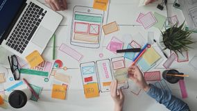 UX-ontwerpers die post-itnota's over app lay-out zetten stock footage