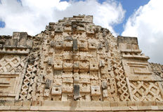 Uxmal. A wall full of engraving of maya gods in the archaeological site of Uxmal (Mexico Royalty Free Stock Photography
