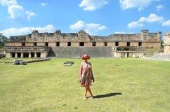 Uxmal, Messico, 2015-04-20: Signora alla moda anziana che sta alla vista delle piramidi antiche maya Immagini Stock Libere da Diritti