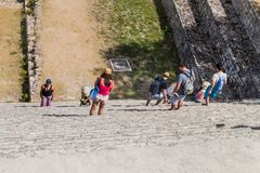 UXMAL, MEXICO - FEB 28, 2016: Tourists descend from the Grand Pyramid at the ruins of the ancient Mayan city Uxmal, Mexi. Co royalty free stock photos