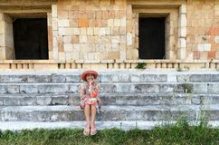 Uxmal, Mexico, 2015-04-20: Old stylish lady sitting at the stairs of ancient pyramid Royalty Free Stock Photography
