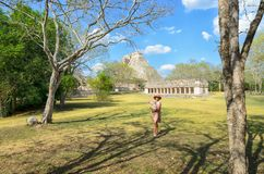 Uxmal, Mexico, 2015-04-20: Old stylish lady standing at the sight of Mayan ancient pyramids stock photos
