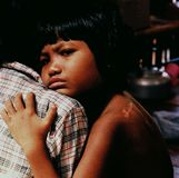 UXO Victim Crying. Paraplegic Cambodian girl is held by her mother at a hospital treating victims of war ordnance left over from the wars in Indochina Royalty Free Stock Image