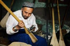 uyghur άτομο που κάνει ένα όργανο αποκαλούμενο dutar μια τοπική έκδοση βιολιών στοκ φωτογραφία