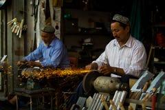 Uyghur Handwerker, die Messer schärfen Lizenzfreies Stockbild