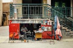 uyghur mężczyzna przy jego pod schody buta remontowym sklepem obraz royalty free